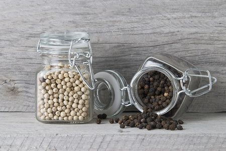 peppercorn: Black and white peppercorns on an old wooden surface. Stock Photo
