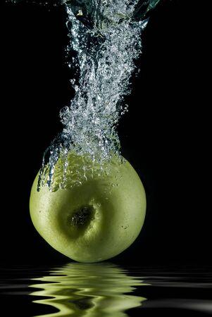 An apple splashing on water.