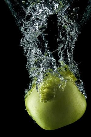 An apple splashing on water. Stock Photo - 9640561