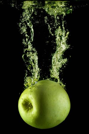 black water: An apple splashing on water.