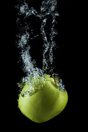 An apple splashing on water. photo