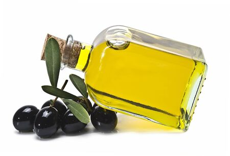 olive green: A bottle of olive oil and some black olives isolated on awhite background. Stock Photo