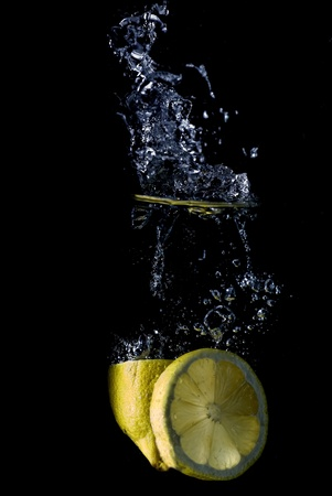 A lemon slid and a half splashing on some water.