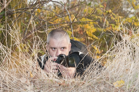 press agent: Photojournalist working in the jungle, camouflaged among the vegetation.