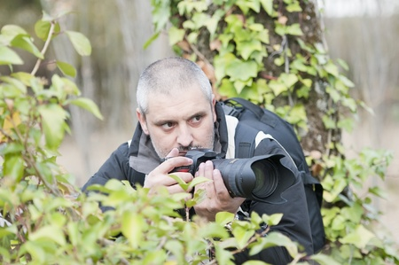 espionage: Photojournalist working in the jungle, camouflaged among the vegetation.