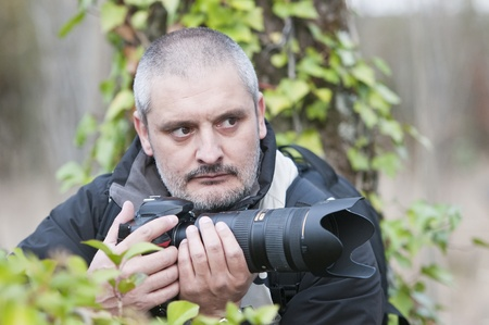 camouflaged: Photojournalist working in the jungle, camouflaged among the vegetation.
