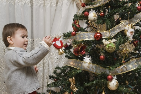 impressed: Little child impressed by his first time decorating the Christmas tree. Stock Photo