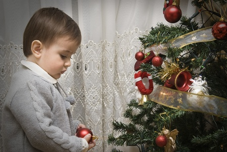 participatory: Little child impressed by his first time decorating the Christmas tree. Stock Photo