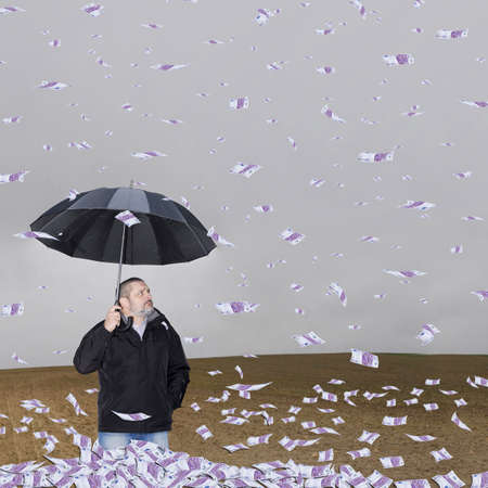 A man with an umbrella in the field amid a storm of money. photo