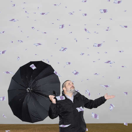 protection plan: A man with an umbrella in the field amid a storm of money.