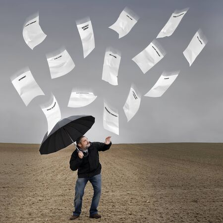 A man with an umbrella daunted by the cost of living and bills falling from the sky. Stock Photo - 11324063