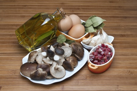 Mushrooms, eggs, ham and olive oil to cook a good menu. photo