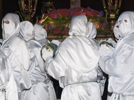 Easter nazarenes in white robe in a typical Spanish procession   photo