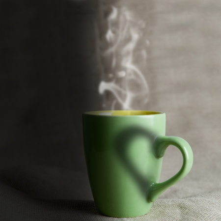A green mug with hot coffee and a heart  photo
