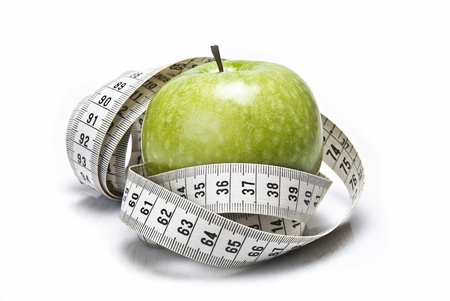 Measuring tape wrapped around a green apple as a symbol of diet. photo