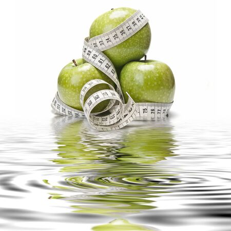 Cinta métrica envuelto alrededor de una manzana verde como símbolo de la dieta. Foto de archivo