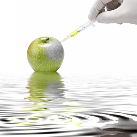 A gloved hand injecting an apple with a syringe on a white background. photo