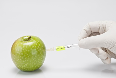 syringe pump: A gloved hand injecting an apple with a syringe on a white background.