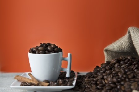 Cup of coffee and beans on an orange vintage background. Stock Photo - 13796976