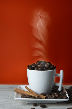Cup full of coffee beans recently roasted and hot. photo