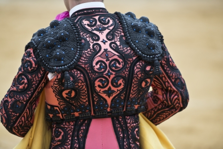 Detail of the jacket of the bullfighter in pink and black amber colors