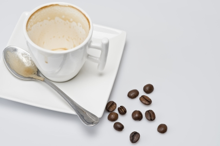 An empty cup of coffee and some coffee beans. photo