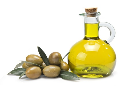 A jar with olive oil and some green olives isolated over a white background.
