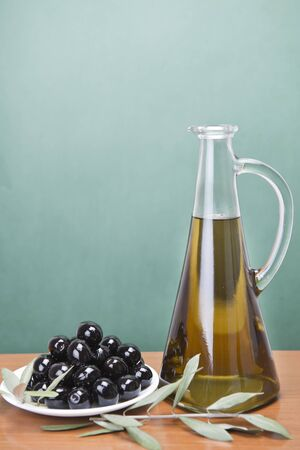 A jar with olive oil ans a plate with black olives on a wooden surface. photo