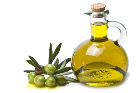 A jar with olive oil and some green olives isolated over a white background