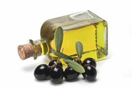 aceite de oliva: Un frasco con aceite de oliva y unas aceitunas negras aisladas sobre un fondo blanco