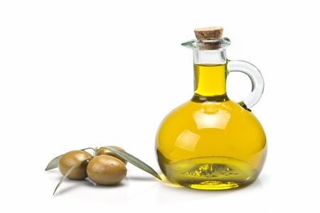 aceite de oliva: Un frasco con aceite de oliva y unas aceitunas verdes aisladas sobre un fondo blanco Foto de archivo