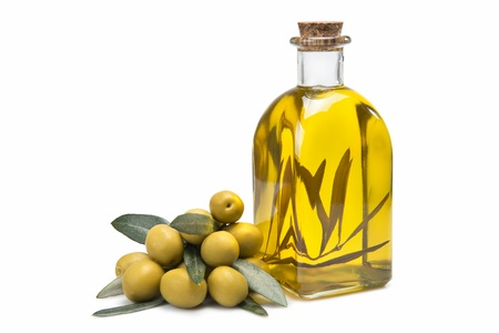 salad dressing: A jar with olive oil and some green olives isolated over a white background