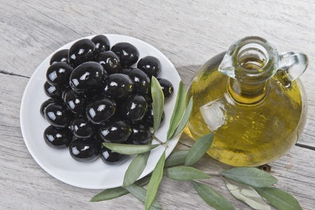 A jar with olive oil ans a plate with black olives on a wooden surface  photo