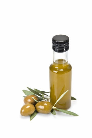 Glass bottle of premium virgin olive oil and some olives with leaves isolated on a white background Stock Photo - 15445333