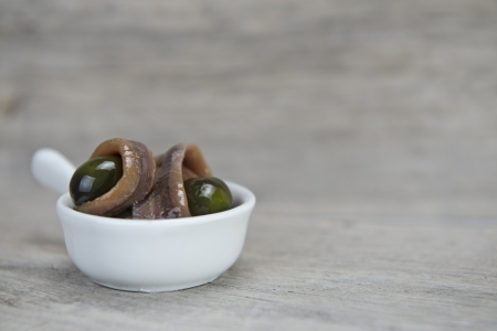 briny: Anchovy appetizer served with green olives in a china spoon on a wooden background