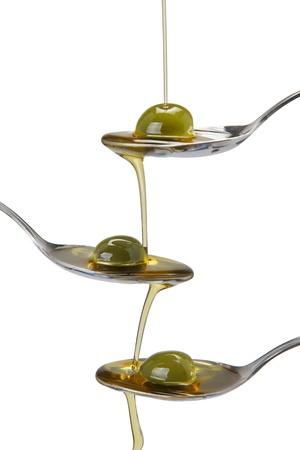 aceite de oliva: El aceite de oliva vertido en una cuchara y la ca�da de una a otra cuchara Foto de archivo