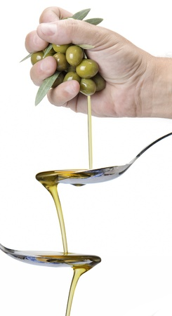 A hanful of olives dropping olive oil into a spoon 写真素材