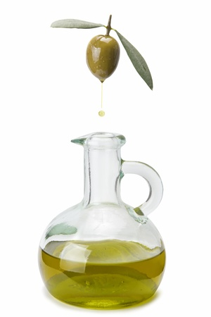 A drop of olive oil falling from one olive into a bottle photo
