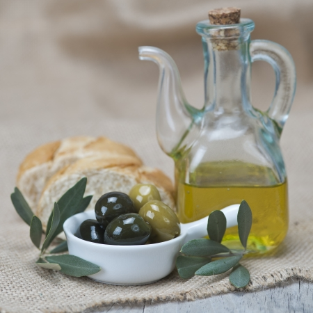 Olive oil with green olives and bread on a wooden surface