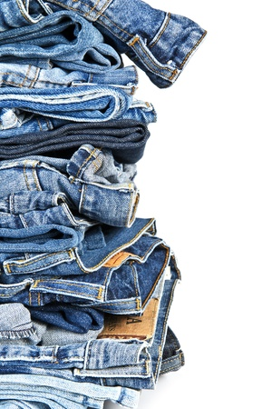 worn jeans: Stack of old and worn blue jeans over a white background Stock Photo
