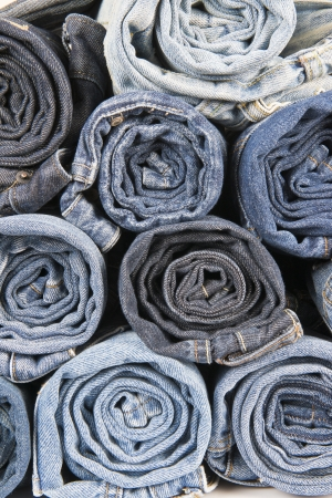 Rolls of different worn and old blue jeans stacked