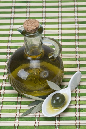 A bottle of olive oil  and a china spoon with olives on a bamboo mat photo