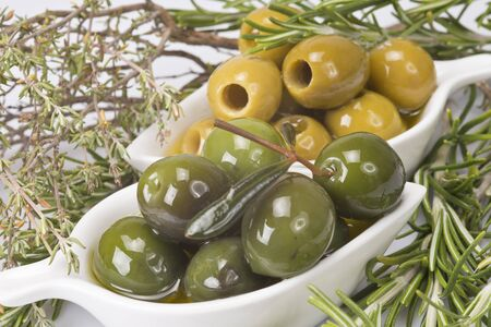 Two china spoons with green and pitted olives and some aromatic herbs Stock Photo - 16565292