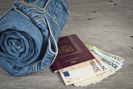 Rolled jeans, a passport and a lot of money on a wooden background photo