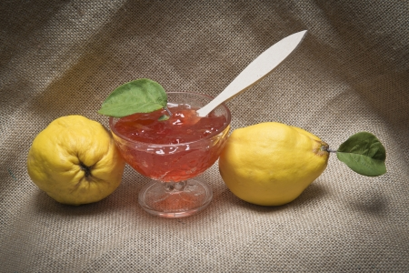 Still life with quinces and quince jelly in a glass cup photo