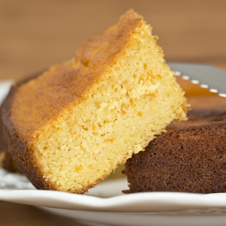 spongy: A cut homemade cake showing its texture on a wooden surface.