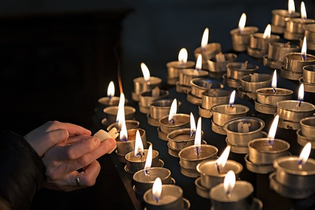 A womand lights candles in a church while her child put his hand on hers  photo