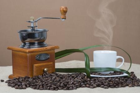 molinillo: Naturaleza muerta sobre el café con tazas, frijoles y un molino