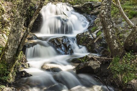 conveys: Cascades on a mountain river with a silky effect on the water that conveys a sense of relaxation.