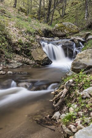 Cascades on a mountain river with a silky effect on the water that conveys a sense of relaxation. photo